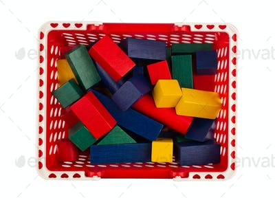 red plastic shopping cart with wooden construction blocks on whi