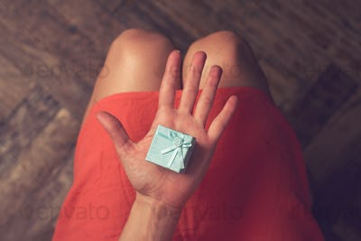 Woman holding a cardboard small gift blue box with ribbon