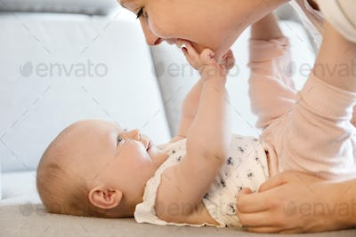 Smiling cute baby girl playing with her caring mother
