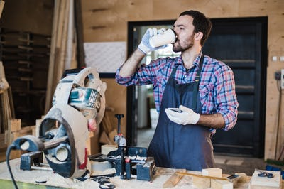 Coffee mug for good work. Thoughtful young male carpenter holding cup while standing near the wooden