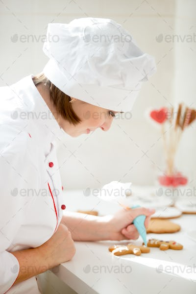 Professional female confectioner bent decorating a gingerman