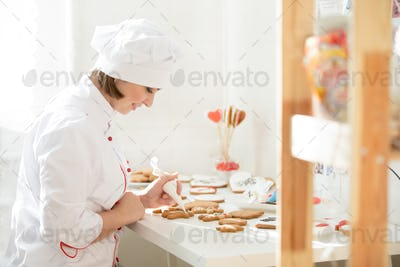 Professional female confectioner sitting and decorating a ginger