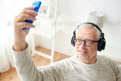 senior man with smartphone and headphones
