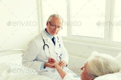 doctor checking senior woman pulse at hospital