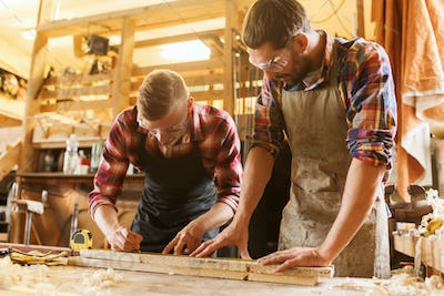carpenters with ruler and wood plank at workshop