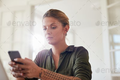 Beautiful young woman using mobile phone at home
