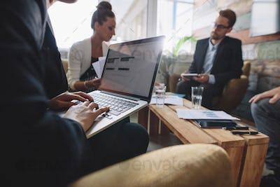 Businesswoman working on laptop during meeting