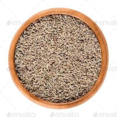 Anise seeds in wooden bowl over white