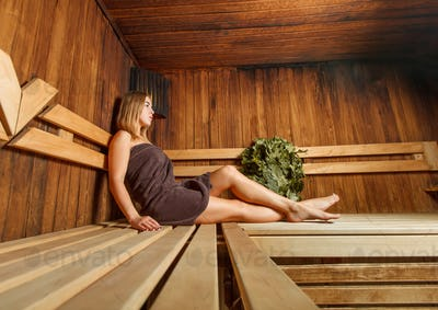 Beautiful woman takes relaxation in the sauna.
