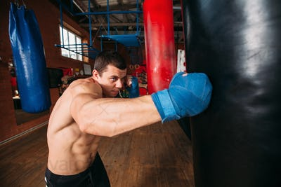 Boxer training with punching bag.