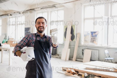 Happy young painter holding paint brush and showing it to camera