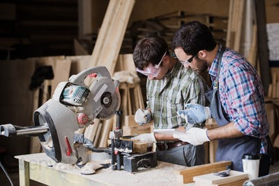 Inspector and carpenter discuss the process of making wood products for furniture