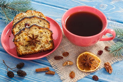 Cup of coffee, fresh baked fruitcake for Christmas and spruce branches