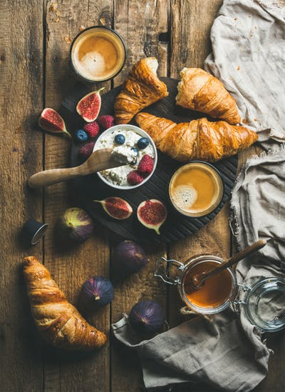 Breakfast with croissants, ricotta, figs, fresh berries, honey and espresso