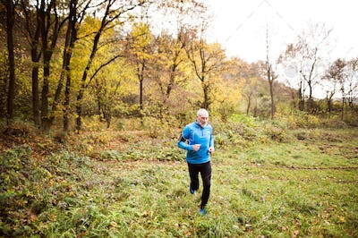Senior man running in nature with smart phone and earphones.