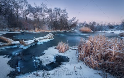 Winter landscape with snowy trees, beautiful frozen river at dus