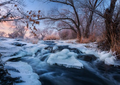 Winter landscape with snowy trees, beautiful frozen river at sun