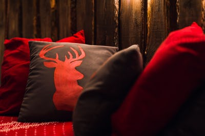 Deer head on red hand made pillow wooden background in interior