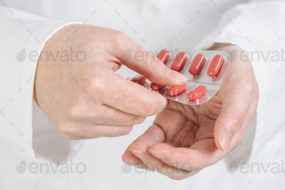 Female doctor offering red tablets to patient