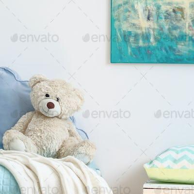 Beige teddy bear on a blue bed
