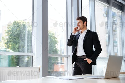 Smiling businessman standing and talking on cell phone in office