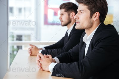Two confident young businessmen sitting in office