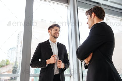Two cheerful young businessmen talking in office