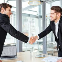 Two cheerful businessmen shaking hands on business meeting