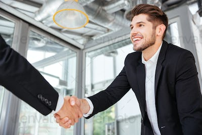 Two successful businessmen shaking hands on business meeting in office