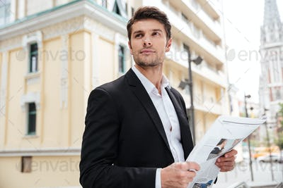 Businessman with newspaper standing on the street