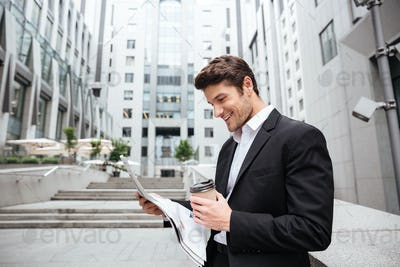 Cheerful young businessman reading newspaper and drinking coffee