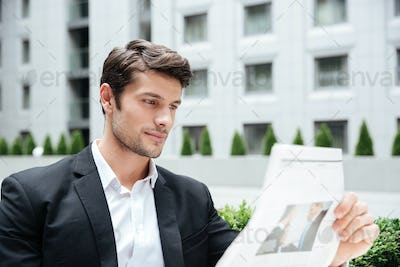 Businessman in suit reading newspper outdoors