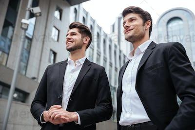 Two businessmen standing near business center