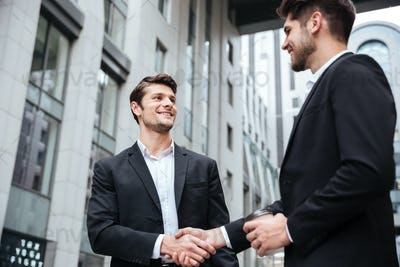 Two cheerful young businessmen shaking hands