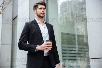 Businessman walking and drinking coffee outdoors