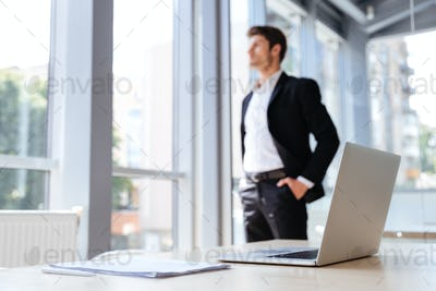 Businessman with laptop and documents standing near the window