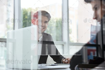 Two cheerful young businessmen with laptop on business meeting
