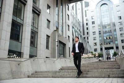 Businessman walking outdoors near business center