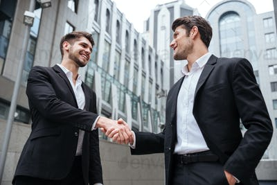 Two happy businessmen standing and shaking hands near business center