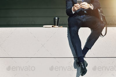 Crop businessman sitting with phone in hands