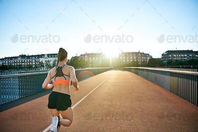Rear view of woman sprinting down bridge