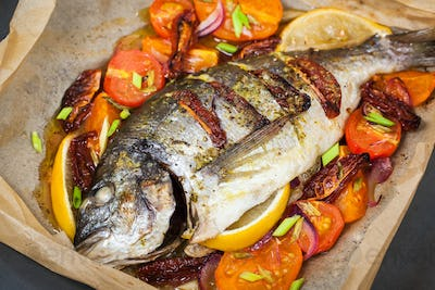 Oven baked whole sea bream fish (dorado) with vegetables