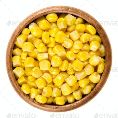 Sweet corn kernels in wooden bowl over white