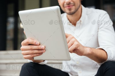 Businessman holding and using tablet outdoors