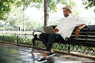 Smiling hipster with laptop in park