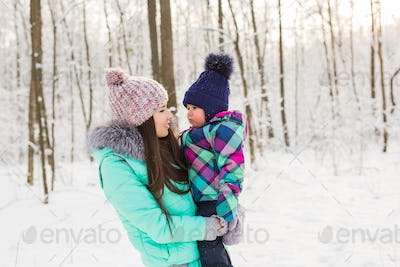 Portrait of happy mother and baby in winter park