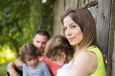 Beautiful young family against old wooden fence. Summer nature.