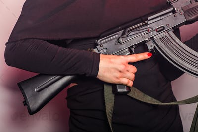 Kalashnikov assault rifle close-up in the woman's hand