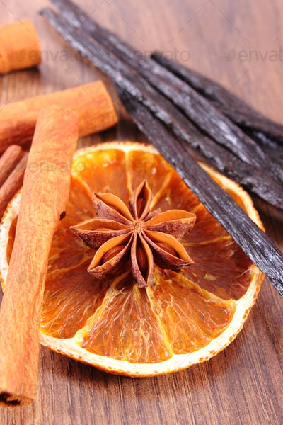 Star anise, fragrant vanilla, cinnamon and dried orange on wooden surface