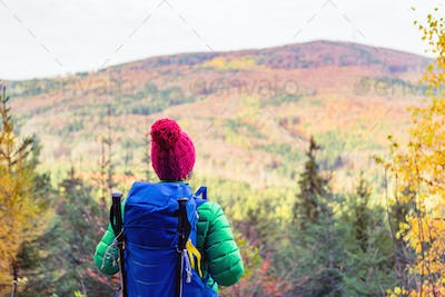 Hiking woman with backpack looking at inspirational autumn mount